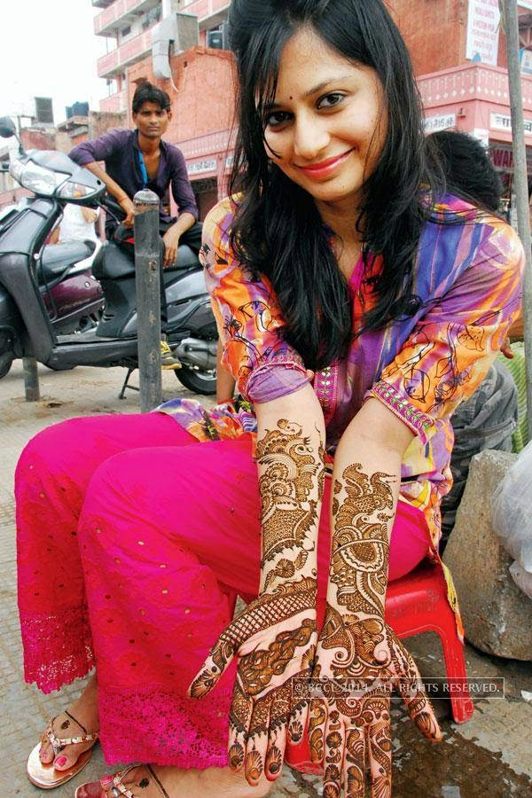 A woman shows off her mehendi design, in Jaipur.