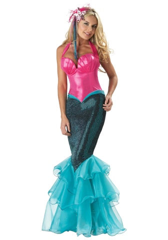 a full length photo of a woman standing against a white background with a mermaid costume on, blue tail skirt and pink bralette top.