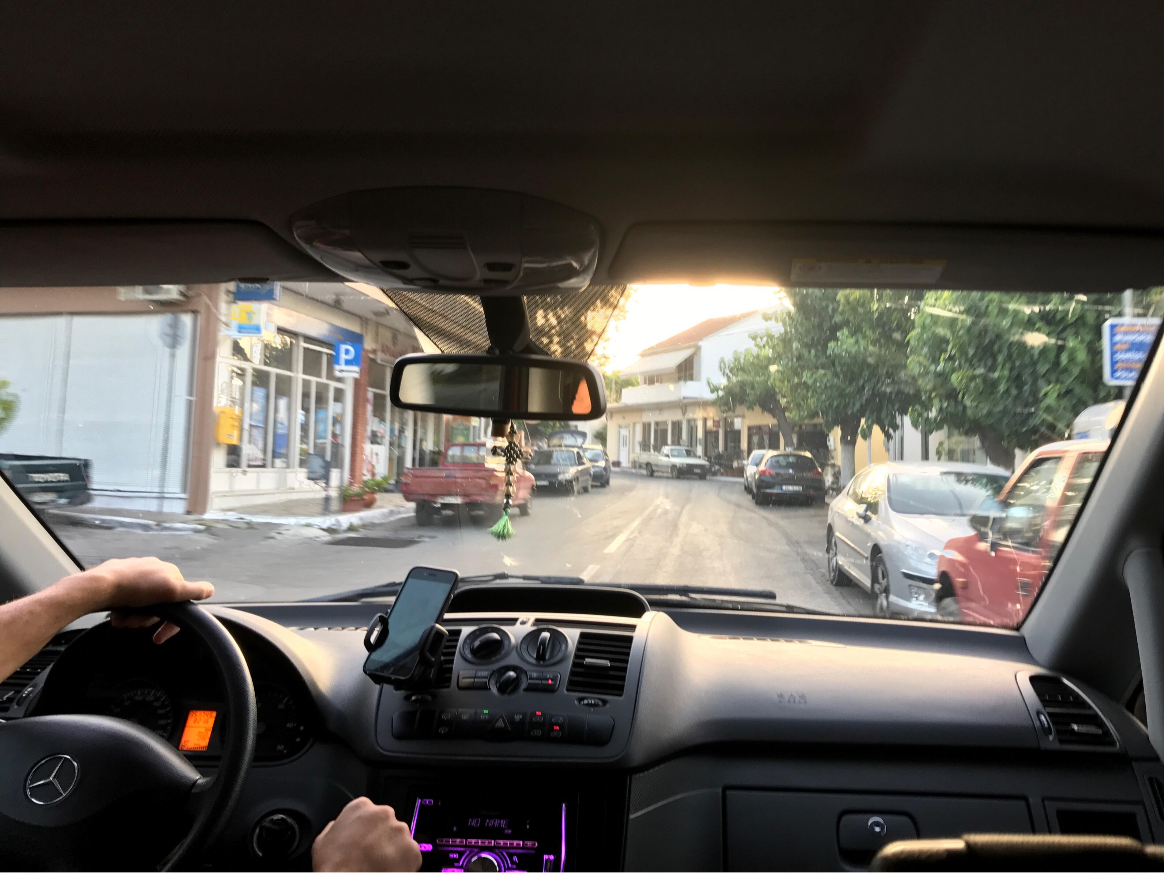 Bilde tatt gjennom frontruta. Bilen kjører gjennom en liten by.