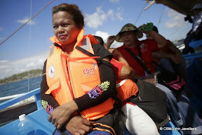 People on a boat, wearing lifejackets and looking determined