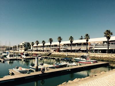En lang bygning med serveringssteder langs en marina.