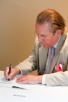 "Author Gene Wilson signs his book, ""Kings of the Hilltop."""