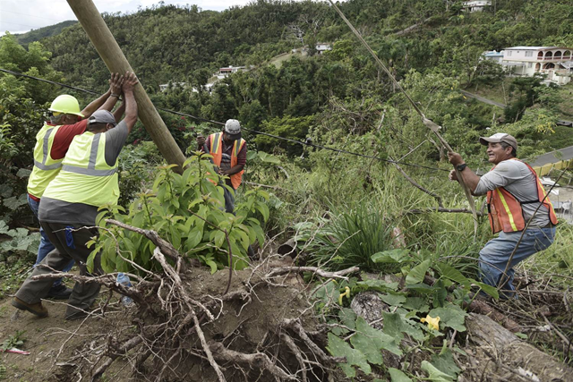 Public Works Sub-Director Ramon Mendez, left, works with locals municipal workers to install a new electrical post in Coamo, Puerto Rico, on 31 January 2018. Photo: Carlos Giusti / AP