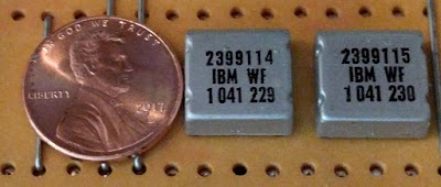 Two IBM SLT modules, with a penny for scale. Each module contains semiconductors (transistors or diodes) and printed resistors wired together, an alternative to integrated circuits.