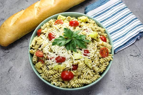 A Large Bowl Of Zucchini Pesto Pasta Salad With Bread On The Side.