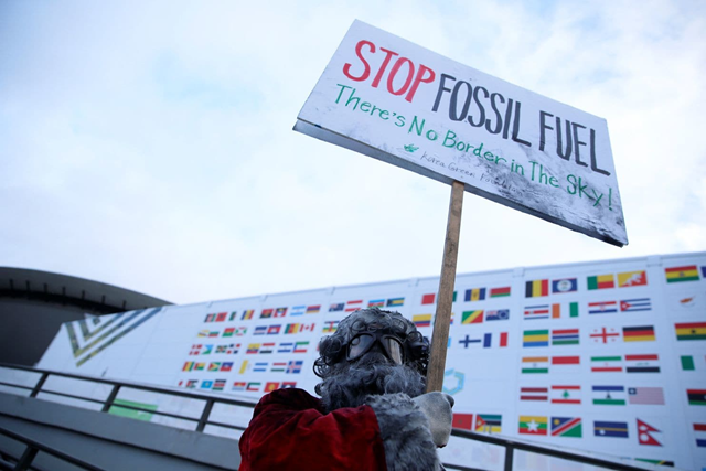 An environmental activist protests fossil fuel production on 10 December 2018 in front of the venue hosting the U.N. climate change summit in Katowice, Poland. Photo: Grzegorz Celejewski / Agencja Gazeta / Reuters