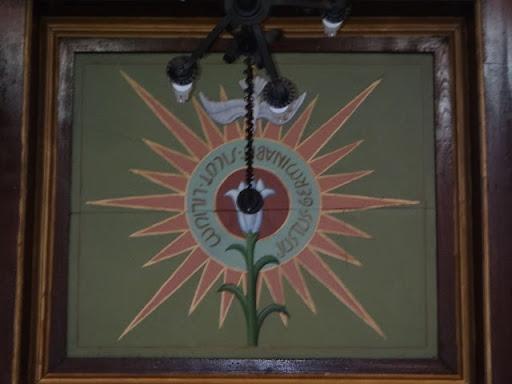 """Detalhe do teto: A arte revela o Espírito Santo e o lírio, representado a castidade. A frase em latim significa """" O justo florirá como um lírio""""."""