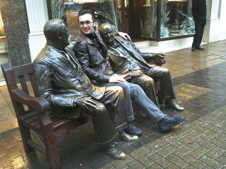 Tur til London og Filippinene: Jeg (Tor-Ivar Krogsæter) sittende en benk i London sammen med et par venner (statuer).
