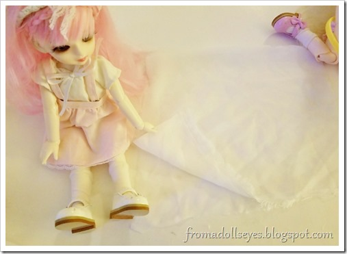 The pink haired bjd (Yuna) is folding a piece of fabric in half.