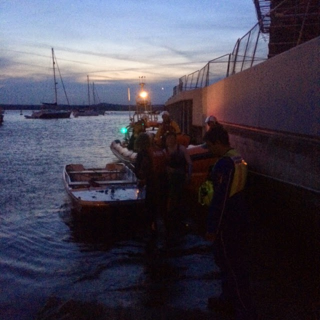 Poole ILB crew meeting Poole Coastguard after they brought a small tender ashore after it was stuck on the mud with another vessel and six people in the fading light on Friday 6 June 2014 Photo: RNLI Poole/Paul Taylor