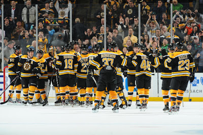 Bruins players celebrate Patrice Bergeron's game winning goal in overtime