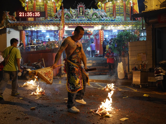 man next to a fire in a ceremony at the Chang Qing Temple (長慶廟) in Taipei