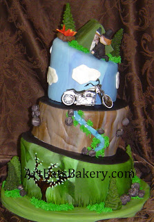 Mad hatter camping wedding cake with trees, rocks, waterfall, motorcycle,  Bride pulling Groom into tent and campfire