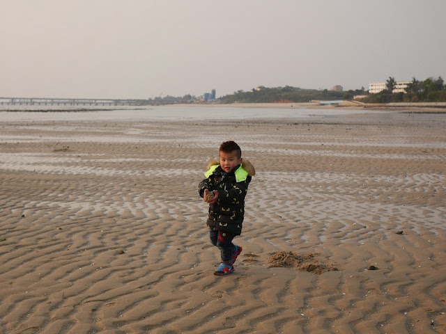boy holding sand during low tide at a beach in Kinmen