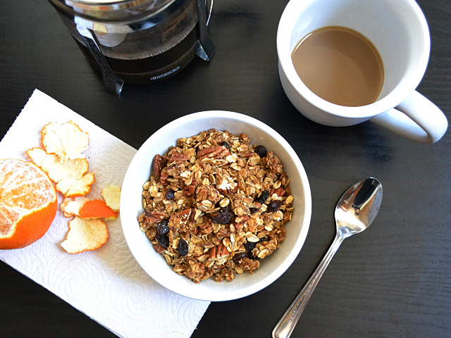 top view of  a bowl of cinnamon pecan granola with a cup of coffee and and orange on the side