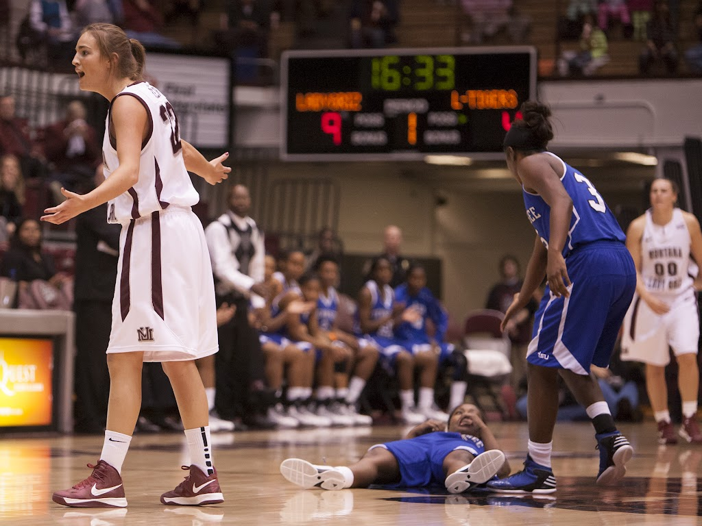 Tennessee's Donyeah Mayfield (#33) lends a helping hand while Montana's Katie Baker appeals to the zebras after a controversial charge was called at halfcourt.  Dahlberg Arena at Missoula, Mont., December 1st, 2012.