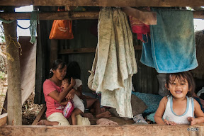 A young woman and three young children in a makeshift wooden shelter surrounded by bedding