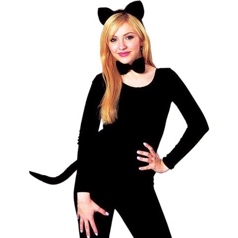 a woman standing against a black background with a full one piece black cat suit, a black stick on tail and cat ears.