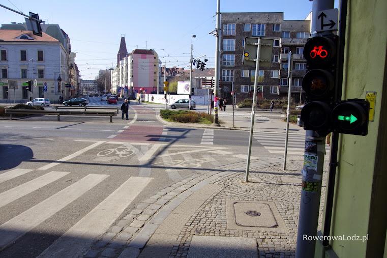 Sygnalizacja dla rowerów wyposażona w zielona strzałkę. Strzałki nad sygnalizatorem rozwiewają wątpliwości w jakich kierunkach można jechać.