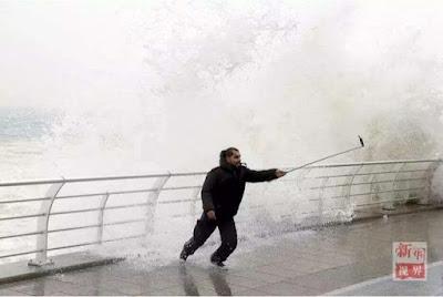 laki-laki yang selfi pada saat gelombang laut tinggi datang