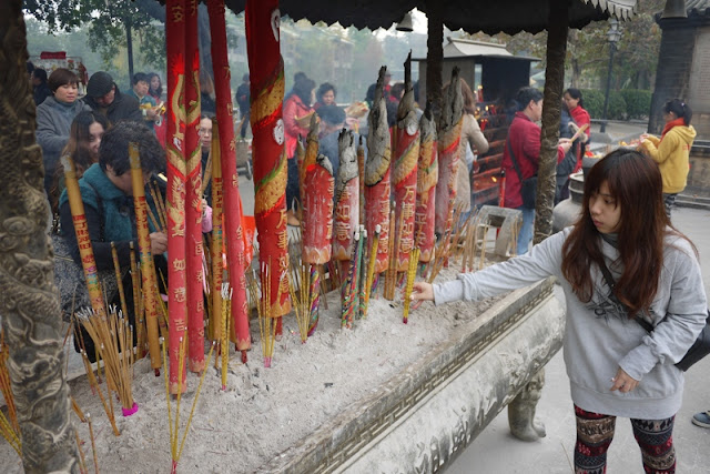 young woman placing incense sticks at Guangzhou's Renwei Taoist Temple