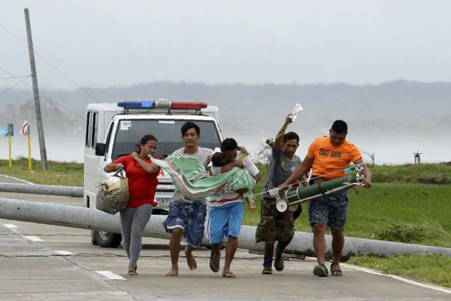 A father carries his sick child to another car as their ambulance is stuck on a highway by toppled electric posts caused by strong winds after Typhoon Mangkhut hit Baggao town in Cagayan province, north of Manila, on 15 September 2018. Photo: Ted Aljibe / AFP / Getty Images