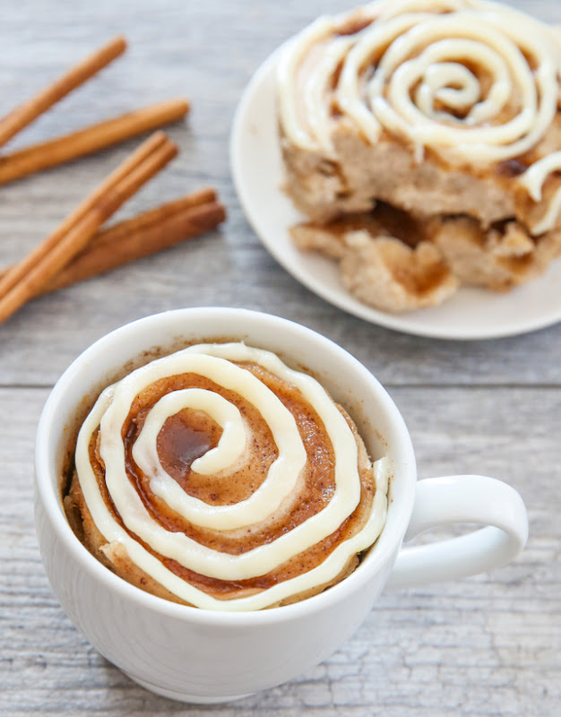 photo of a cinnamon Roll Mug Cake with a cinnamon roll cake on a plate in the background