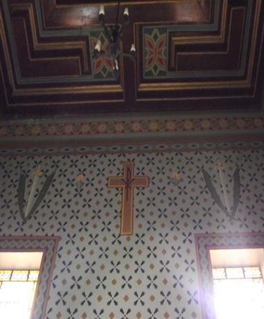 Ao lado da cruz de Cristo tem-se duas figuras iguais representadas por duas palmas e a espada. A palma simboliza a vitória em Cristo pelo martírio. Assim, a espada representa o sofrimento do martírio e a palma a vitória pelo martírio.