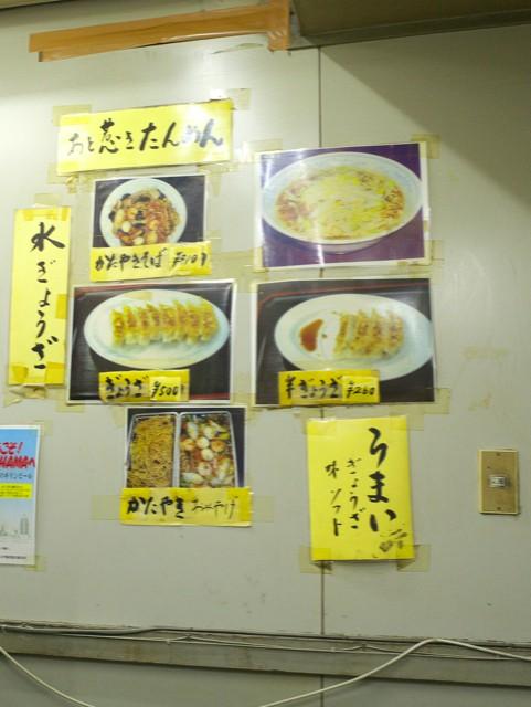 壁にはられた写真付きメニュー。手書きで「うまい、ぎょうざ、味ソフト」と書かれてる