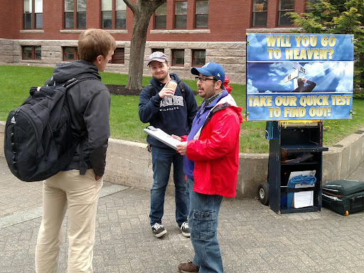"""It was cold and rainy, but that didn't stop over 400 students from taking gospel tracts from us, as well as over a dozen fruitful conversations, like this one with Garrett (left.) Garrett thought he was good enough to gain God's approval without Jesus. Tyler (center) was listening in. Tyler is a Roman Catholic student who believes his """"religion"""" will save him. Please pray that both these gentlemen realize that their own goodness is worthless, and that's why Jesus sacrificed Himself on the cross."""