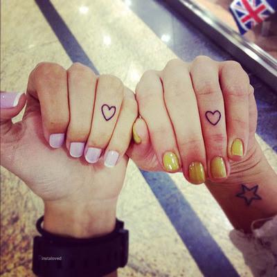 Pequeno coracao tatuado no dedo do anel e estrela no pulso, olhando incrivel