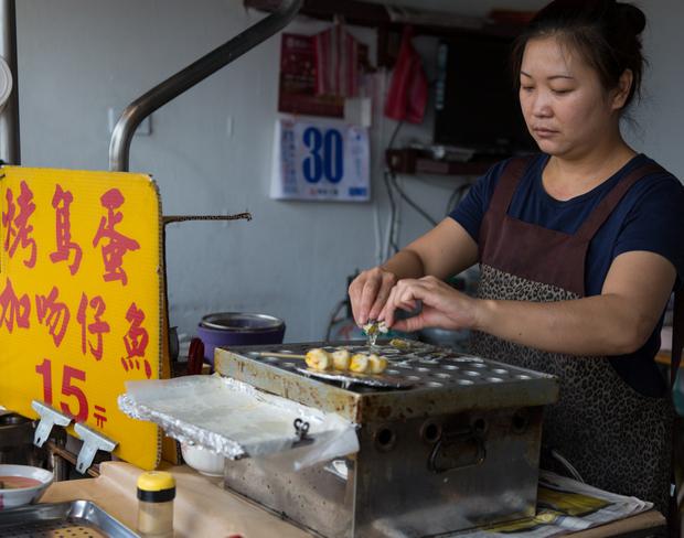 photo of a woman making quail egg skewers
