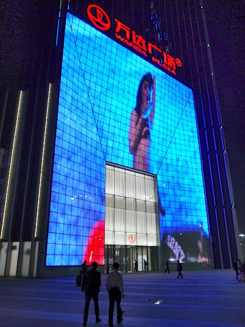 large screen surrounding entrance to Kaifu Wanda Plaze in Changsha displaying video of a female singer