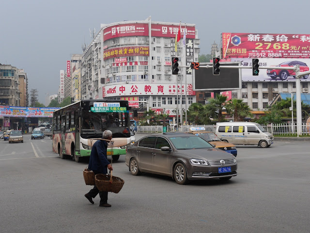 man carrying two baskets on a pole across the intersection of Wuyi Road and Dongfeng Road