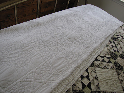 A white-on-white quilt drapes the bottom of this bed.