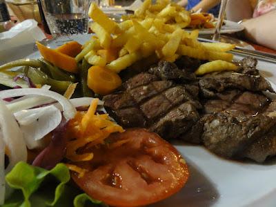 En tallerken med salat, kjøtt og pommes frites.