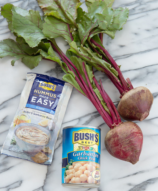 overhead photo of fresh beets, a can of garbanzo beans, and a package of hummus made easy