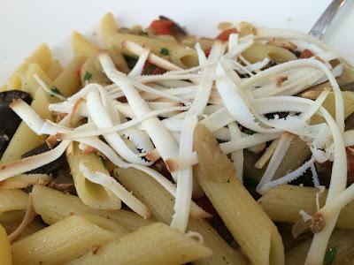 Pastarør blandet med stekte grønnsaker og strimler av ost på toppen.