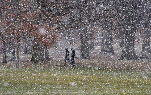 People cross Flagstaff Hill as snow falls in Schenley Park in the Oakland section of Pittsburgh on Tuesday, 20 March 2018. Photo: Darrell Sapp / Pittsburgh Post-Gazette / AP