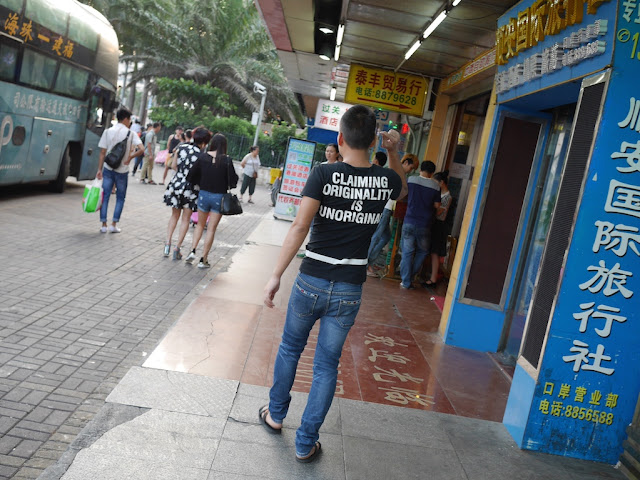 "man wearing shirt with ""CLAIMING ORIGINALITY IS UNORIGINAL"" on back"