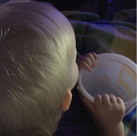 Kind schaut fernsehen und hält einen Eimer