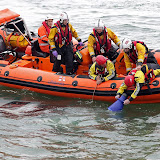 A fireman uses a special device to peer through the water at the submerged vehicle, whilst an RNLI crew member keeps hold of him - 27 October 2014.  Photo credit: Sally Adams/Bournemouth Echo