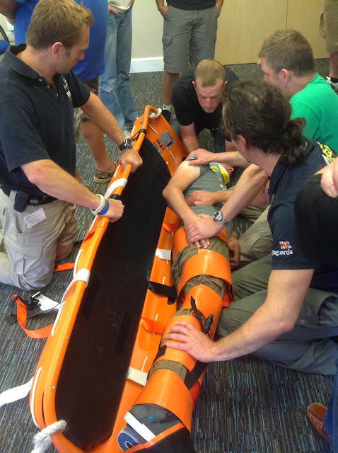 Crew Member Joe being log rolled into the basket stretcher after being immobilised in a collar and fracture straps - July 2014 Photo: Dave Riley