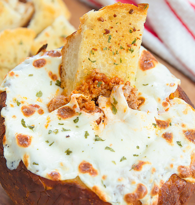 bread slice dipped into the lasagna bread bowl dip