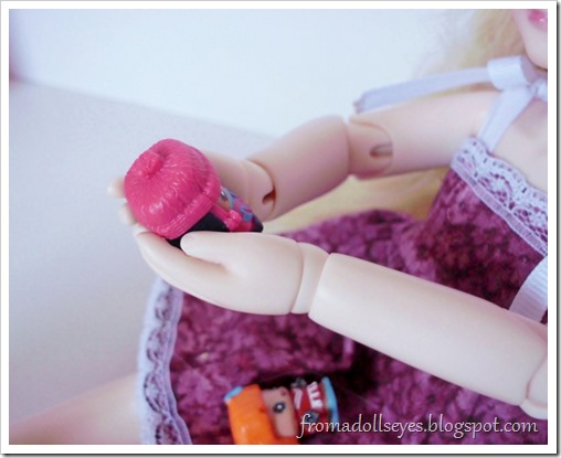 A ball jointed doll holding a My Mini Mixie Q's figure.