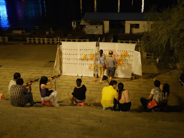 several people shooting balloons at night in Hengyang, China