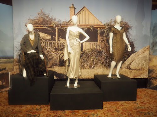 Three costumes from The Dressmaker, set in front of country house. Mannequin in wheelchair wearing cardigan and skirt, mannequin in ballgown and mannequin in structured dress.