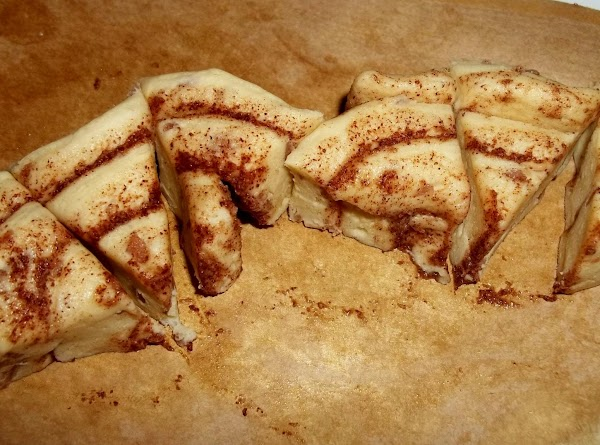 Open the cans of cinnamon rolls and separate into individual rolls. Cut each of...