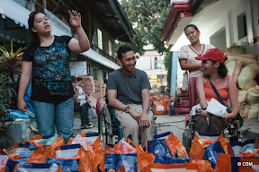 Four people smiling, in front of large orange bags (two of the people are wheelchair users)