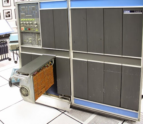 The IBM 1401 computer, with one of the gates opened, showing the dozens of circuit boards (SMS cards) in each gate.  The fan on the front of the gate keeps the cards cool.